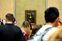Povo aglomerado pra ver a Monalisa, ou só pra fazer uma selfie do lado dela